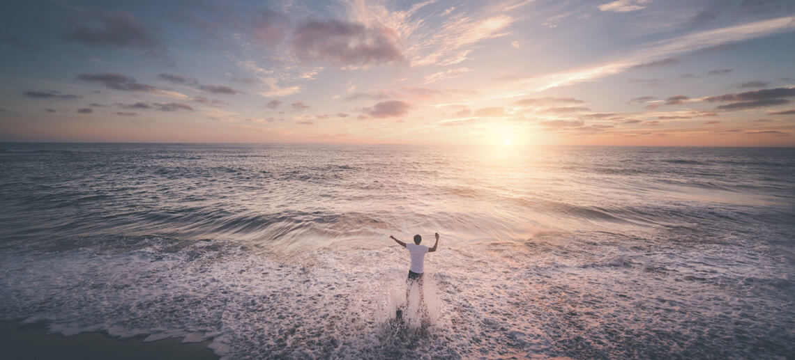 man standing in the waves on a beach with his arms lifted up high and the sun setting on the waves