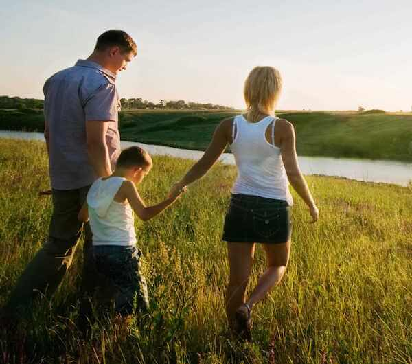 after the successful rapid opiate detox procedure, a father, mother and child walk hand in hand through a field of knee high grass toward a body of water