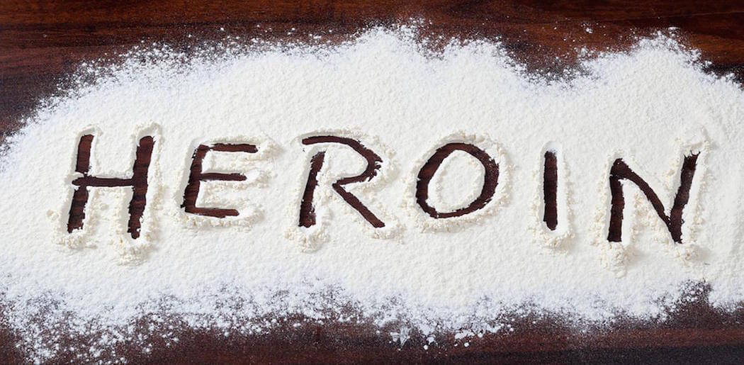 rapid heroin detox center picture of heroin spread across the surface of the table where a finger has written in the heroin powder the word heroin in capital letters